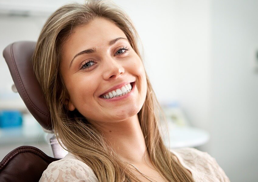 smiling young woman sitting in a dental chair