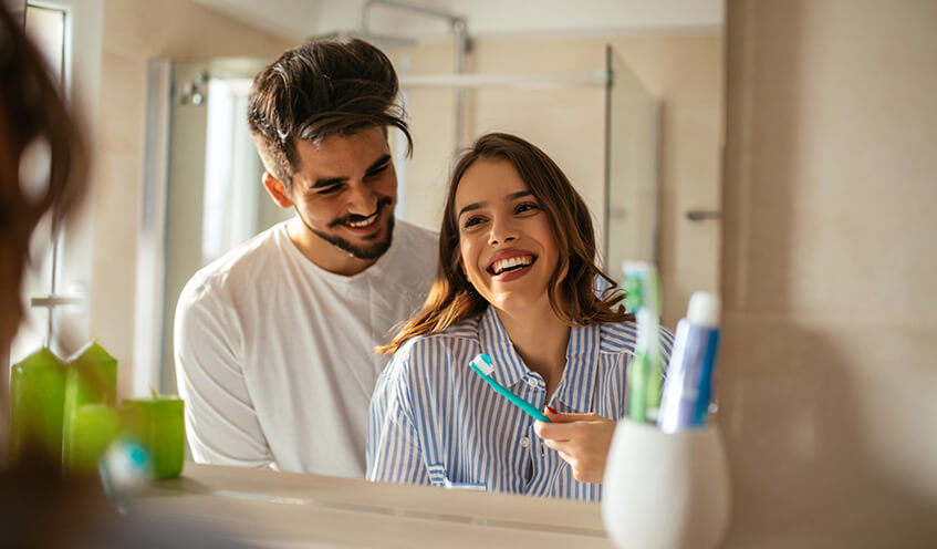 young happy couple brushing their teeth