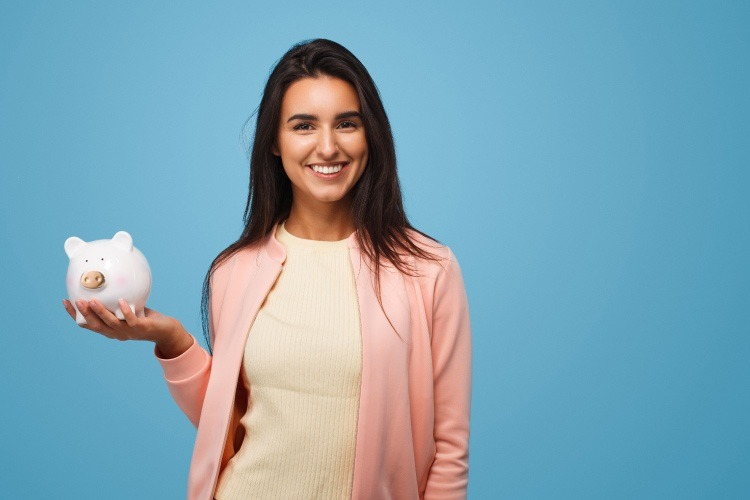 Brunette woman wearing a pink cardigan holds up a white piggy bank for saving money against a blue wall