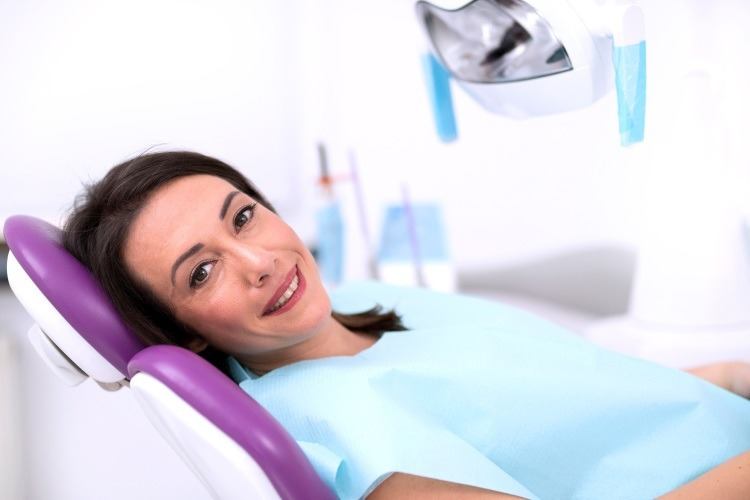Smiling brunette woman in dental chair waiting for a dental implant