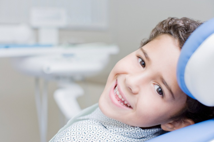 Smiling dark haired young boy in a dental chair