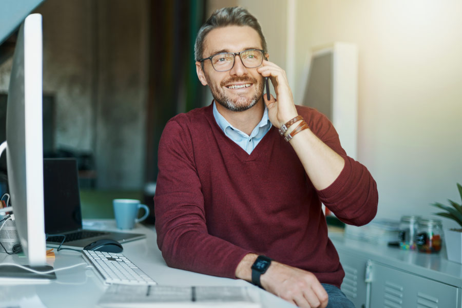 Smiling man on the phone in his home office