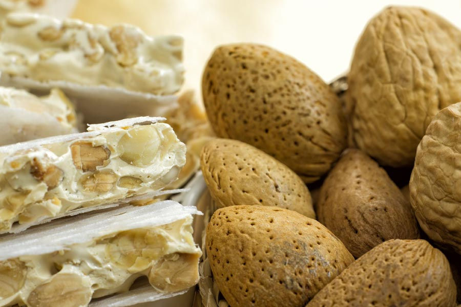 Photo of chewy white nougat and nuts in shells