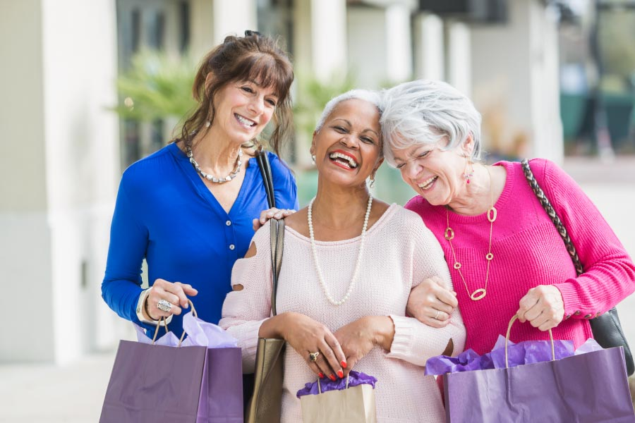 Three smiling mature women walking down the street together arm in arm with shopping bags.